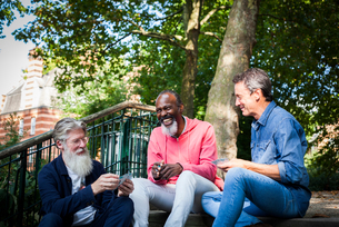 Three mature men, outdoors, sitting on steps, playing cardsの写真素材 [FYI03606128]