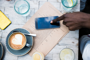 Coffee, mobile phone, menu on wooden tableの写真素材 [FYI03606140]