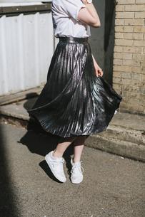 Woman in street twirling metallic skirtの写真素材 [FYI03606246]