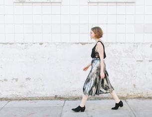 Woman in metallic skirt walking in street, full length, side viewの写真素材 [FYI03606251]