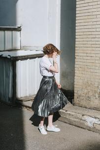 Woman in street twirling metallic skirtの写真素材 [FYI03606255]