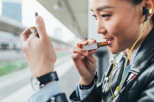 Woman sitting on train platform, applying lipstick, wearing earphonesの写真素材 [FYI03606346]