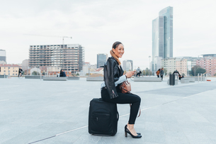 Portrait of businesswoman outdoors, sitting on suitcase, smilingの写真素材 [FYI03606363]