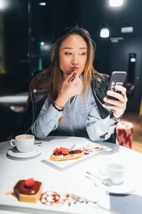 Woman sitting in restaurant, eating dessert, using smartphoneの写真素材 [FYI03606388]