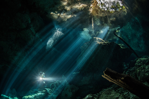 Male diver diving in underground river (cenote) with sun rays and rock formations, Tulum, Quintana Rの写真素材 [FYI03606500]