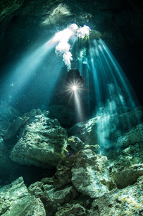Male diver diving in underground river (cenote) with sun rays and rock formations, Tulum, Quintana Rの写真素材 [FYI03606504]