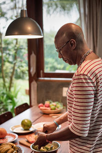 Mature man at kitchen table preparing fruit in bowlの写真素材 [FYI03606530]