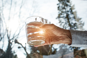 Senior woman holding glass of water, close-upの写真素材 [FYI03606531]