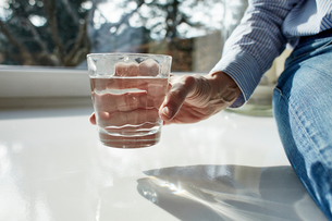 Senior woman holding glass of water, close-upの写真素材 [FYI03606534]