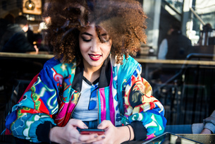 Young girl sitting in bar, using smartphone, view through window, London, England, UKの写真素材 [FYI03606559]