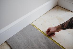 Cropped view of man measuring floor tilesの写真素材 [FYI03606589]