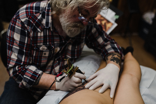 Tattooist tattooing young woman's thighの写真素材 [FYI03606590]