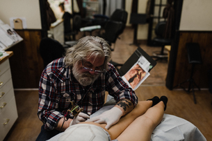 Tattooist tattooing young woman's thighの写真素材 [FYI03606592]