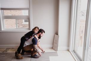 Girl hugging father installing floor tilesの写真素材 [FYI03606595]