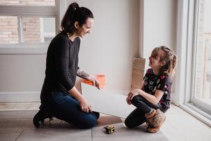 Girl helping mother installing floor tilesの写真素材 [FYI03606597]