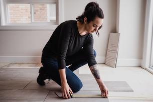 Woman measuring floor tilesの写真素材 [FYI03606598]