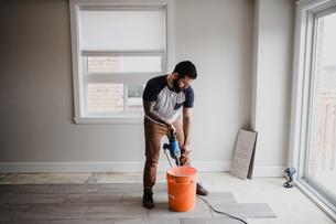 Man mixing cement in bucket with hand mixerの写真素材 [FYI03606599]