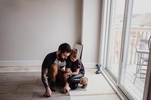 Girl helping father install floor tilesの写真素材 [FYI03606600]