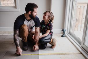 Girl helping father install floor tilesの写真素材 [FYI03606602]