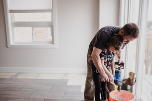 Father and daughter mixing cement in bucket with hand mixerの写真素材 [FYI03606604]