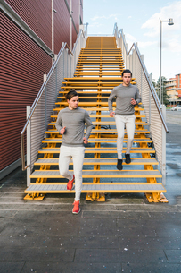 Young adult male twins running together, running down city stairwayの写真素材 [FYI03606762]