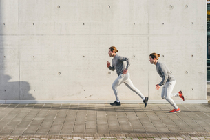 Young adult male twins running together, running up sidewalkの写真素材 [FYI03606763]