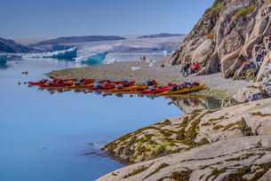 Adventure tourists on fjord beach with rows of kayaks, Narsaq, Vestgronland, South Greenlandの写真素材 [FYI03606895]