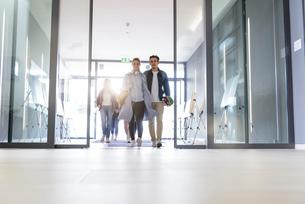 Students entering college building by glass doorsの写真素材 [FYI03606958]