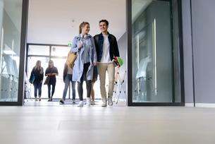 Students entering college building by glass doorsの写真素材 [FYI03606960]