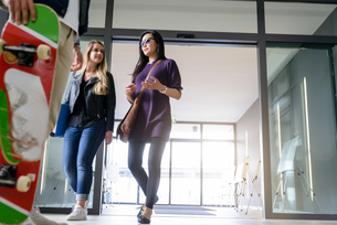 Students entering college building by glass doorsの写真素材 [FYI03606961]