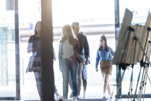 Students entering college building by glass doorsの写真素材 [FYI03606962]