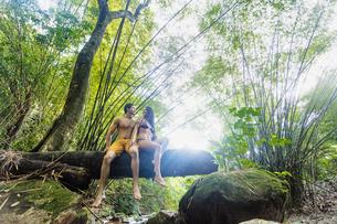 Couple on tree trunk over stream in rainforest, Guaiuba, Ceara, Brazilの写真素材 [FYI03606989]