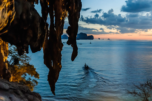 Overhanging rock, boat and sunset in background, Tonsai, Krabi, Thailandの写真素材 [FYI03606990]