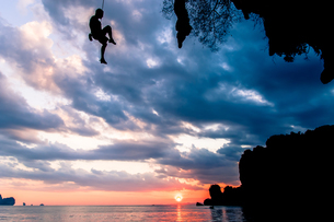 Rock climber suspended over sea at sunset, Tonsai, Krabi, Thailandの写真素材 [FYI03606994]