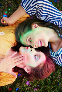 Two young women covered in coloured chalk powder lying on grass at Holi Festival, overhead viewの写真素材 [FYI03607055]