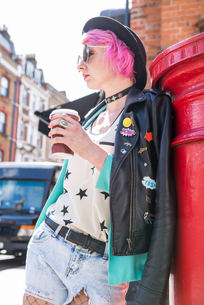 Young woman with pink hair and quirky style leaning against red mailbox, London, UKの写真素材 [FYI03607063]