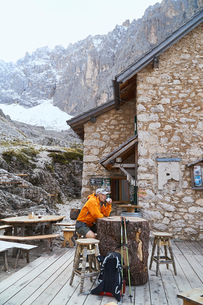 Hiker relaxing with cup of coffee, Canazei, Trentino-Alto Adige, Italyの写真素材 [FYI03607121]