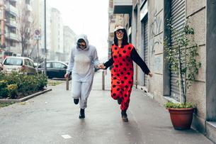 Women wearing adult bodysuits holding hands in streetの写真素材 [FYI03607203]