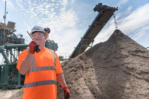 Worker talking on walkie talkie with crusher and concrete screening machine in concrete recycling siの写真素材 [FYI03607362]