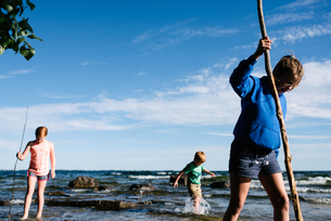 Siblings exploring water with sticks, Kingston, Canadaの写真素材 [FYI03607400]