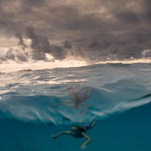 Young boy swimming underwater, split view, Tongaの写真素材 [FYI03607598]
