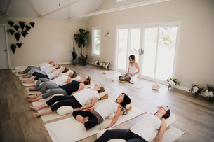 Women in relaxation pose after yoga class at retreatの写真素材 [FYI03607742]