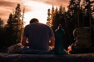 Young male hiker taking a break at sunset, Tuolumne Meadows, upper part of the Yosemite National Parの写真素材 [FYI03607825]