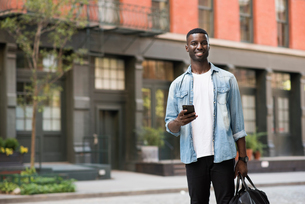 Young man with hand luggage holding cellphone in streets of New York, USの写真素材 [FYI03607942]
