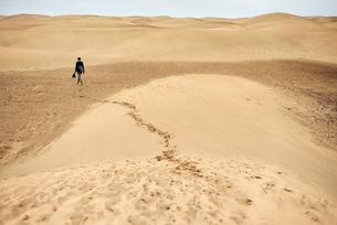 Mature female tourist walking barefoot on sand dune, rear view, Las Palmas, Gran Canaria, Canary Islの写真素材 [FYI03607999]