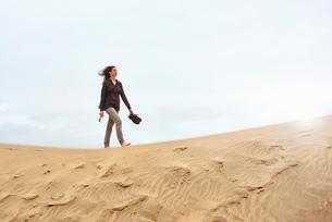 Female tourist walking barefoot on sand dune, Las Palmas, Gran Canaria, Canary Islands, Spainの写真素材 [FYI03608002]