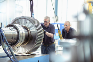 Engineers using crane to move large gear in gearbox factoryの写真素材 [FYI03608145]