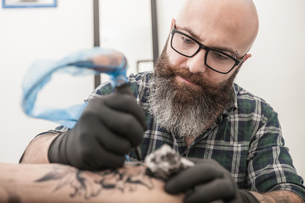 Tattooist drawing on arm of clientの写真素材 [FYI03608246]
