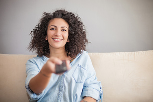 Woman pressing remote control on sofaの写真素材 [FYI03608254]