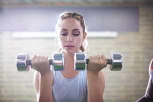 Trainer watching female client lifting dumbbells in gymの写真素材 [FYI03608265]